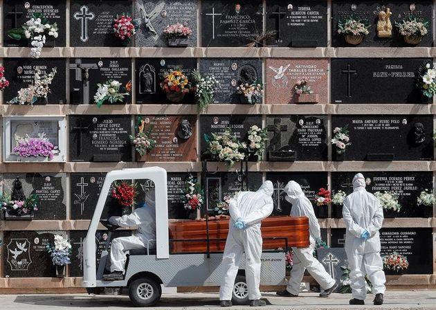 Personal del cementerio del Cabañal, en Valencia, transporta un féretro durante un entierro de una víctima...