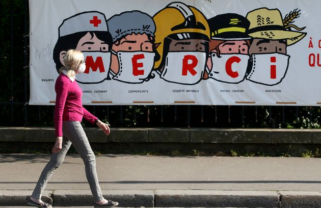 Une femme porte un masque pour se protéger du coronavirus et passe devant une banderole de l'artiste...