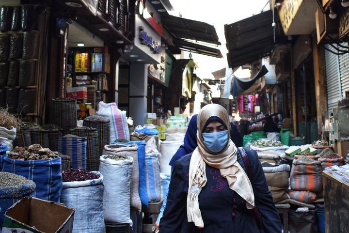 A woman walks through an Al Azhar district street market where people usually buy spices and herbs to prepare for R