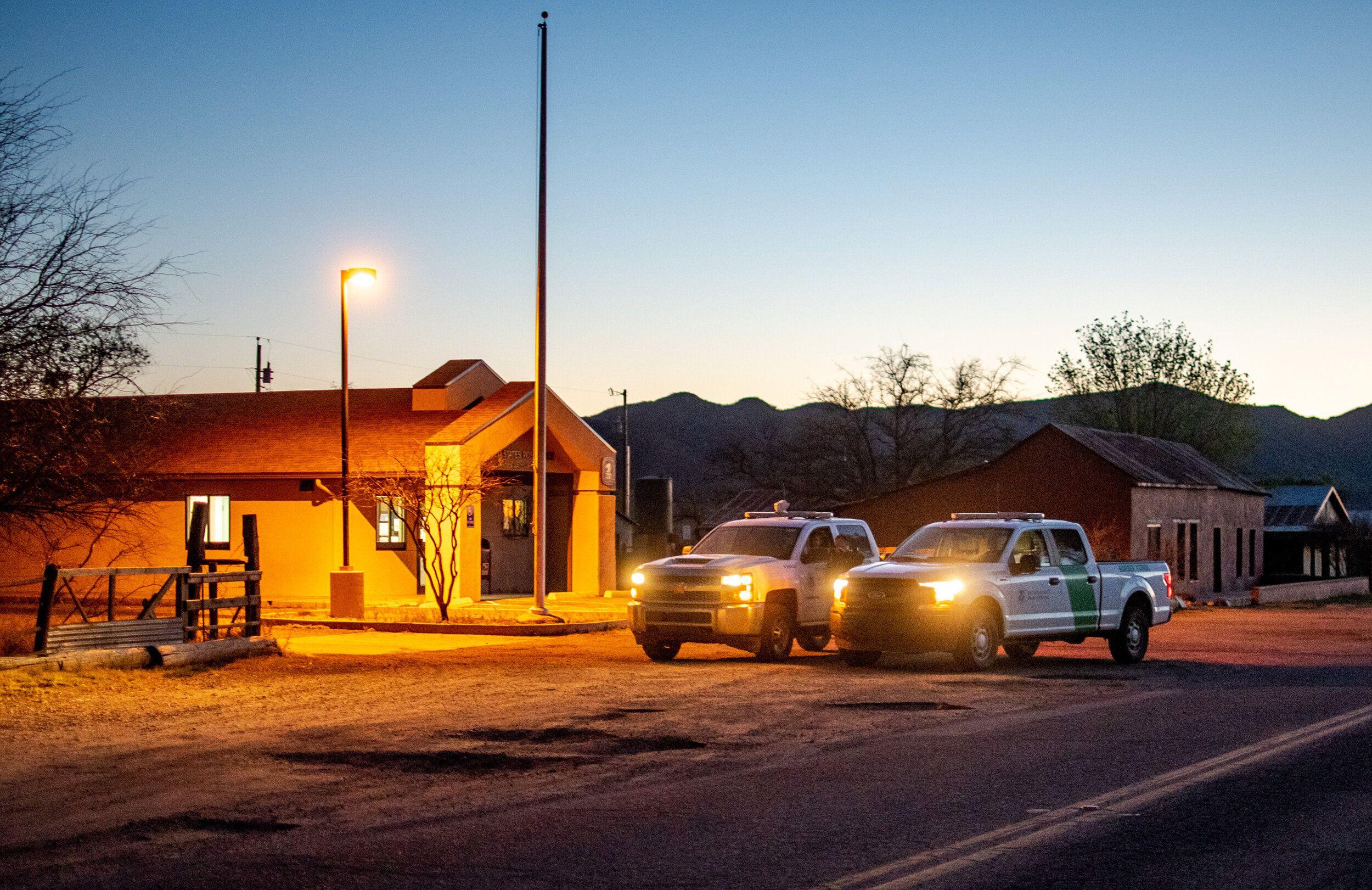 U.S. Border Patrol trucks sit parked on the main road in Arivaca on April 15.