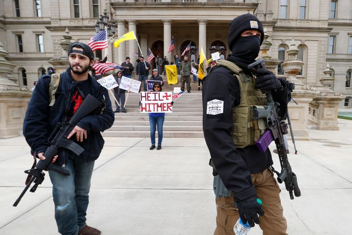 Protesters carry rifles near the steps of the Michigan State Capitol in Lansing on April 15. Flag-waving, honking protesters drove past the Capitol on Wednesday to demonstrate against Gov. Gretchen Whitmer's social distancing measures to slow the spread of the coronavirus.