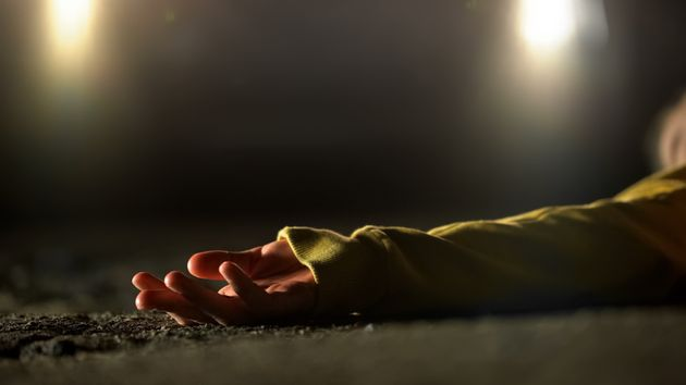 Bloody female victim of deadly car accident lying on road, close-up view at