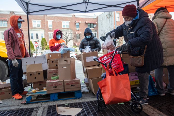 Staff and volunteers distribute food at The Campaign Against Hunger food pantry, Thursday, April 16, 2020, in the Bedford-Stu