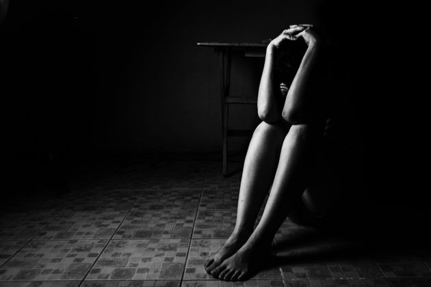 a woman sitting on ground with arm around lower head, sexual violence , sexual abuse, human trafficking...