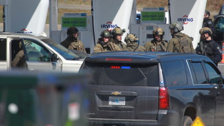 RCMP officers prepare to take a suspect into custody at a gas station in Enfield, N.S. on April 19, 2020.