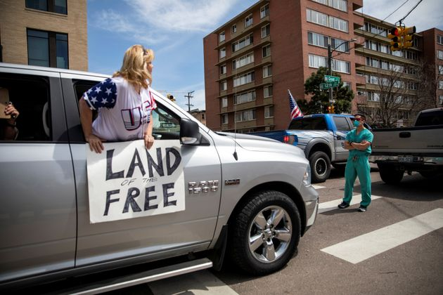 Health care workers stand in the street in counter-protest to hundreds of people who gathered at the...