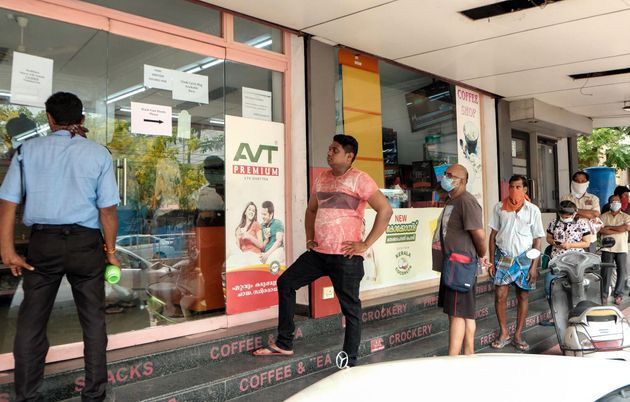 People wait at an ATM counter to withdraw money during the lockdown due to the COVID-19 outbreak in Kochi,...
