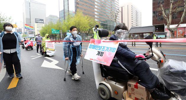 장애인의 날인 20일 오후 서울 광화문광장에서 전국장애인철폐연대(전장연) 회원들이 '420장애인차별철폐 물리적 거리두기 행진'을 하고