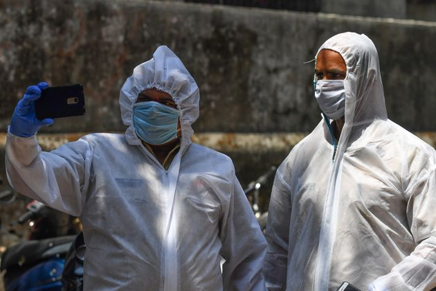 Policemen in hazmat suits at a COVID-19 coronavirus testing drive inside the Dharavi slums in