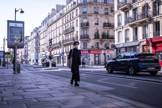 A man wearing a face mask walks along an almost deserted street in Paris, France, during the quarantine...