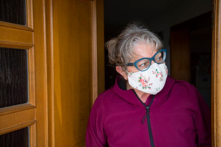 """In this stock photo, a woman in a face-mask leans out her front door. Home-buying is changing in the pandemic, with virtual tours and """"COVID clauses"""" now common."""