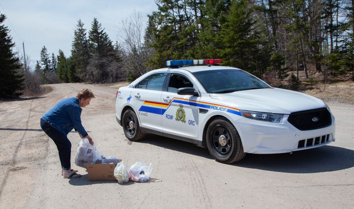 Local resident Juanita Corbett delivers food and drinks to police on Portapique Beach Road after Sunday's deadly shooting rampage on April 20, 2020 in Portapique, N.S.