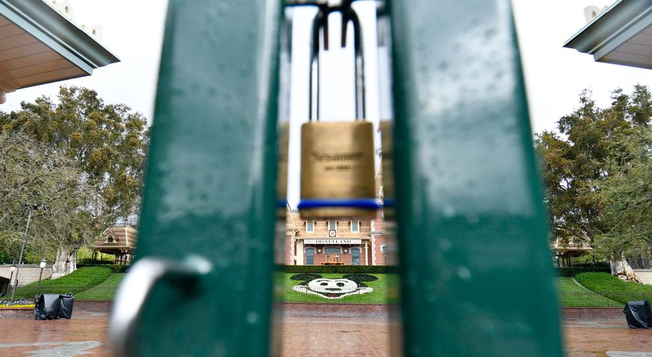 A lock hangs on the center gate between the turnstiles at the entrance to Disneyland in Anaheim, California, on March 16, 2020.