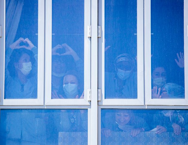 UC Irvine Medical Center health care workers bang on the windows in a return of gratitude as they watch...