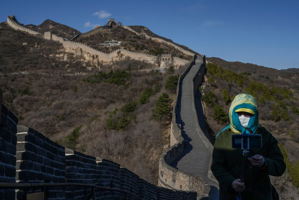 A woman wears a protective mask as she takes a photo on a nearly empty section of the Great Wall on March 27, 2020, near Bada