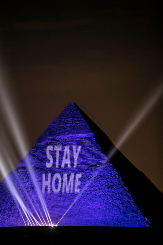 """A picture on April 18, 2020, shows the Great Pyramids lit in blue with the message """"Stay Home"""" outside the Egyptian capital of Cairo."""