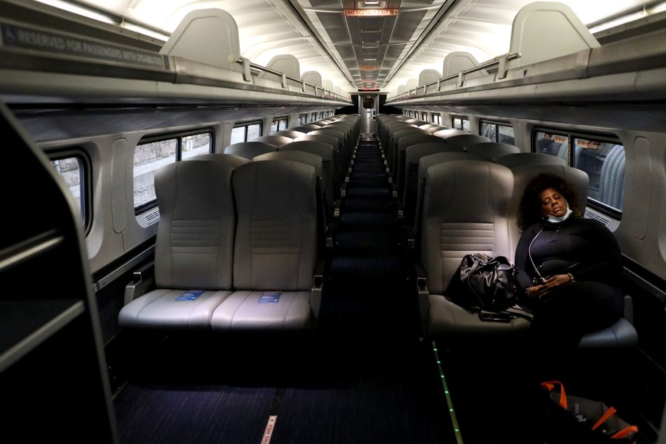 A lone passenger sleeps in an otherwise empty Amtrak car as the train pulls into Penn Station on April 9, 2020, in Baltimore.