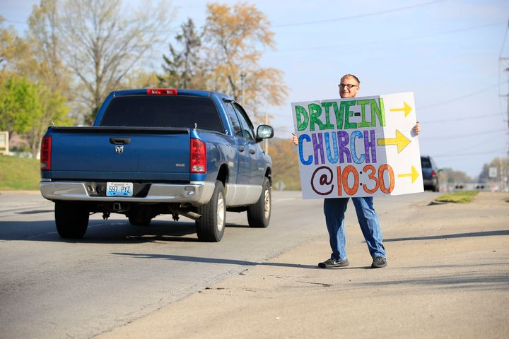 A worshipper holds a sign to alert drivers to a drive-in service at On Fire Christian Church on April 5, 2020, in Louisville,