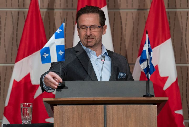 Bloc Leader Yves-Francois Blanchet places Quebec flags on the podium before starting his news conference in Ottawa on April 20, 2020.