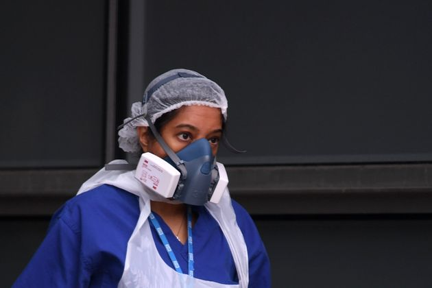 A nurse wears a protective face mask as she walks outside The Royal London Hospital in east
