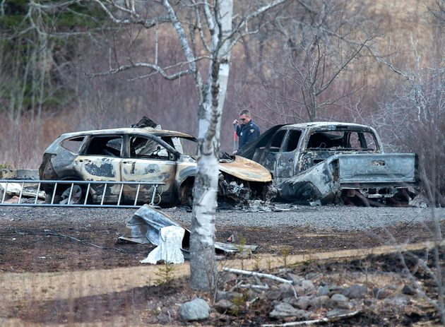 An RCMP investigator inspects vehicles destroyed by a fire on Monday at a residence in Wentworth Centre,