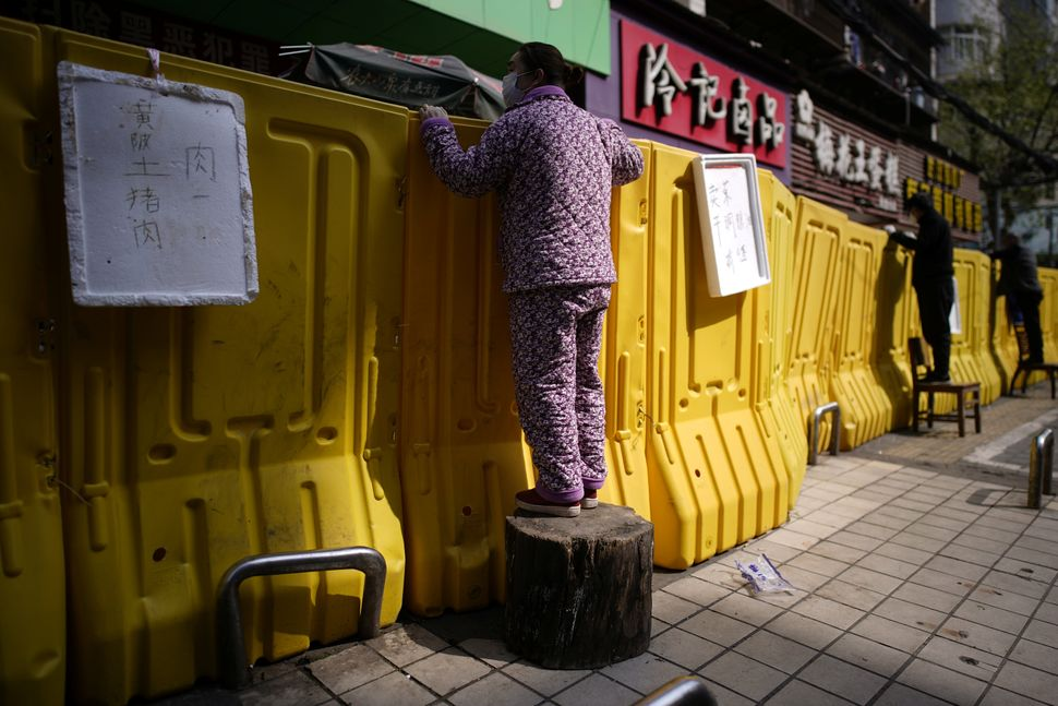Residents pay for groceries by standing on chairs to peer over barriers set up by a wet market on a street in Wuhan, the epic