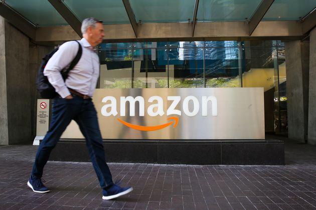 A man walks past an Amazon logo outside a building in Toronto in June