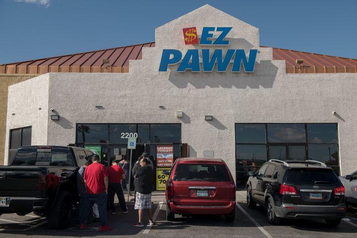 Customers wait in line outside an EZPawn on April 13, 2020, in Las Vegas.