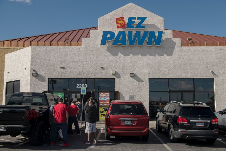 Customers wait in line outside an EZPawn on April 13, 2020, in Las