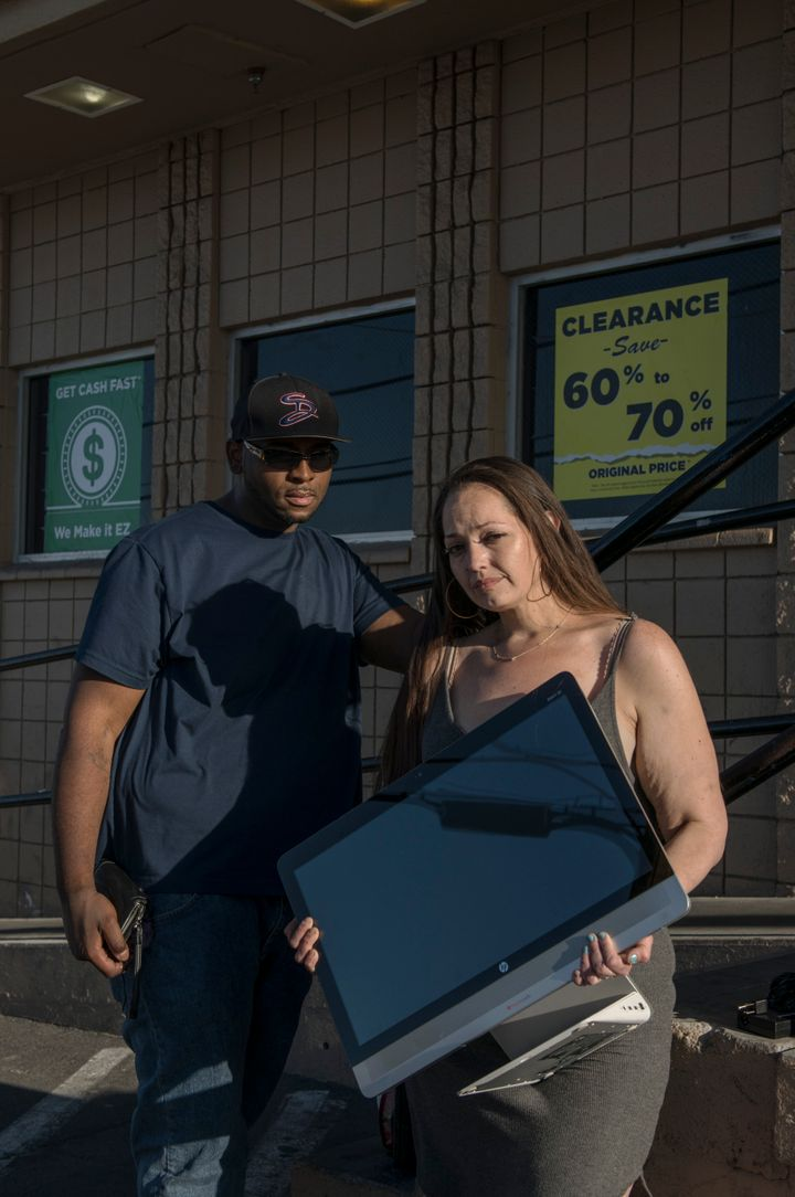 """Cue and Sara Lovato wait in line with a computer they're hoping to sell at an EZPawn on April 13, 2020. """"Gotta get some gas,"""" said Sara. Her work in behavioral health has been affected by the coronavirus."""