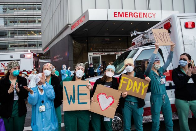 NEW YORK, NY - APRIL 21: Medical workers hold signs outside NYU Langone Health hospital as people applaud...