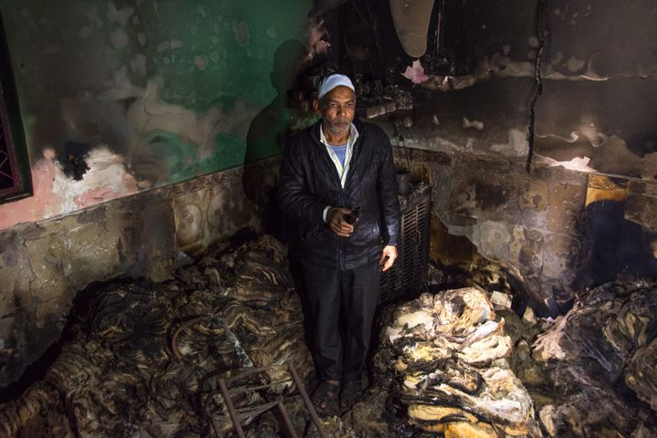 A man grieving inside his burnt factory of Sarees in Shiv Vihar, a neighbourhood that saw some of the worst instances of communal violence in late February.