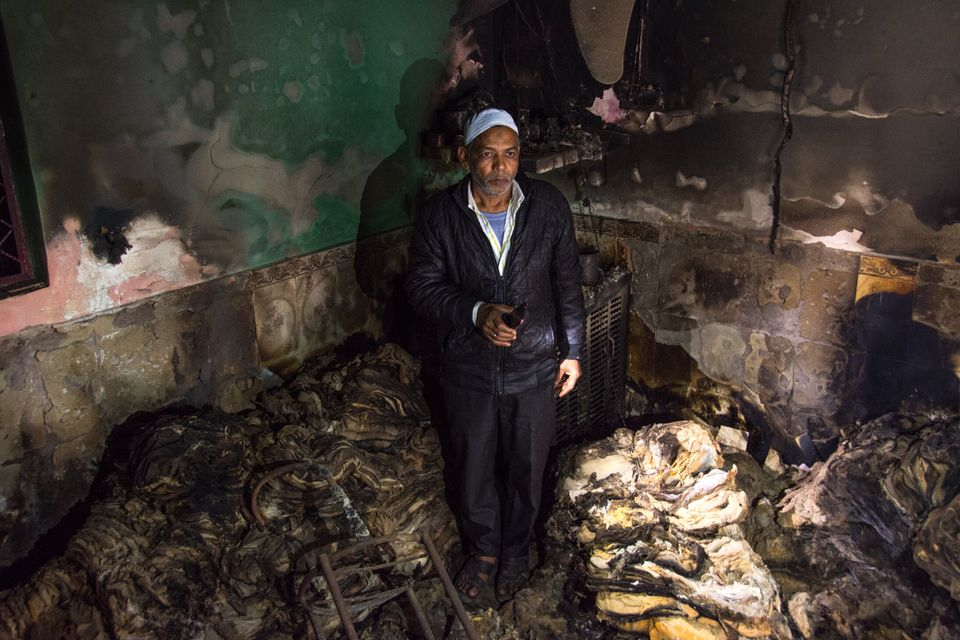 A man grieving inside his burnt factory of Sarees in Shiv Vihar, a neighbourhood that saw some of the...