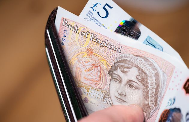A British wallet held open to show newly issued polymer banknotes, with the £10 note featuring the 19th...