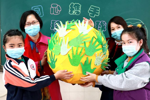 HUZHOU, April 21, 2020 -- Students and their teachers show a model of the Earth during an activity calling...