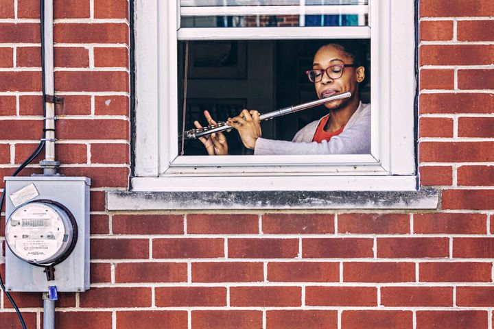 One of Gruenwald's subjects seen playing the flute through her window.