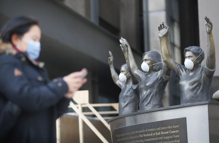 A pedestrian passes statues outside Princess Margaret Hospital in Toronto during the COVID-19 pandemic.