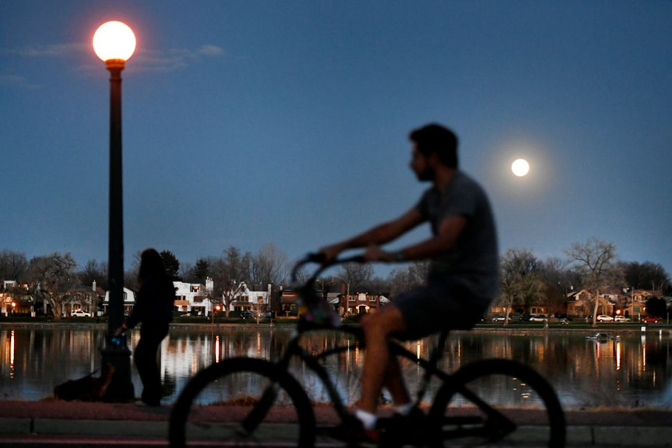 Cyclists and pedestrians pass by Smith Lake in Washington Park on April 7, 2020, in Denver. The city is closing some streets