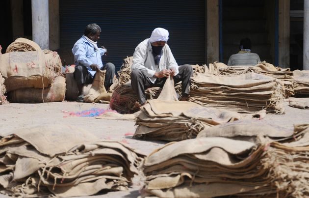 Laborer repairing gunny bags use for carrying Wheat at new grain market lockdown on April 15, 2020...