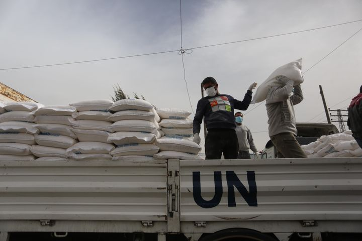Palestinian employees at the U.N. Relief and Works Agency for Palestinian Refugees prepare food aid rations that will be deli