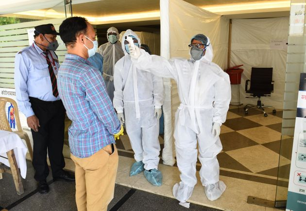 A journalist undergoes thermal screening during a health camp organised for COVID-19 tests at West Patel...
