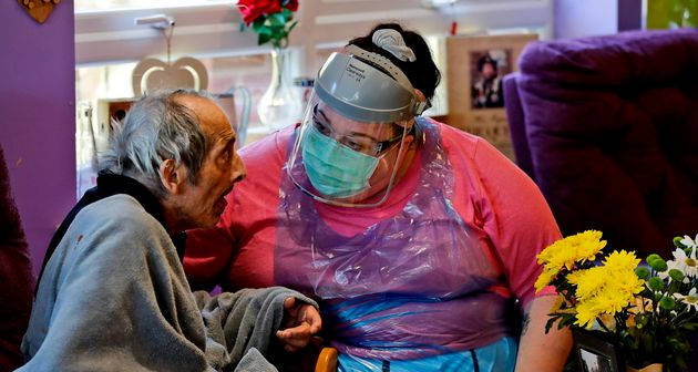 A nurse in PPE speaks to a resident at the Wren Hall care home in Nottingham, Monday, April