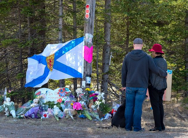 A couple pays their respects at a roadblock Wednesday in Portapique,