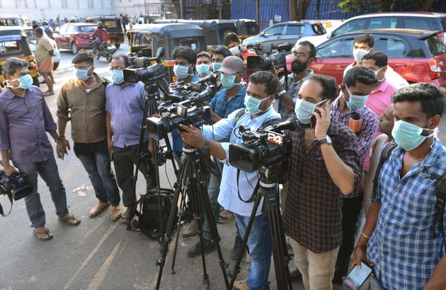 Journalists wearing surgical masks stand outside a government general hospital in Thrissur, Jan. 30,