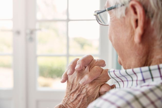Senior man sits looking out of the window at home, close