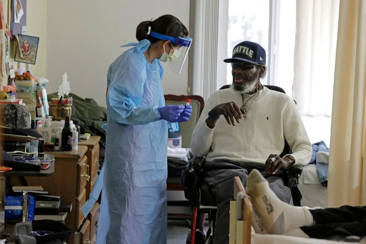 In this Friday, April 17, 2020, photo, Dr. Gabrielle Beger, left, prepares to take a nose-swab sample from Lawrence McGee, as