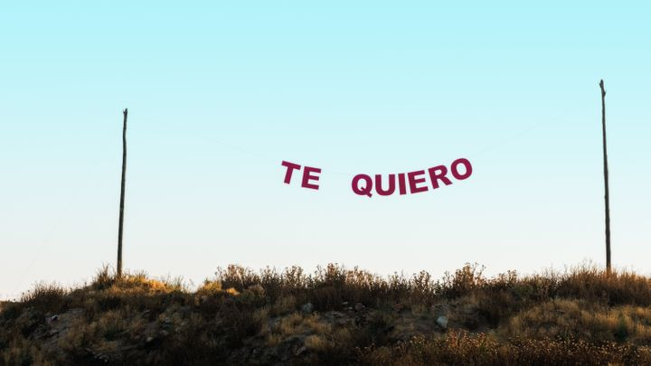 """Words """"te quiero"""" hung between two poles with a rope, in a blue sky. Concept of love."""
