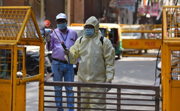 An East Delhi Municipal Corporation (EDMC) worker chemically disinfects an area in Pandav Nagar on April...