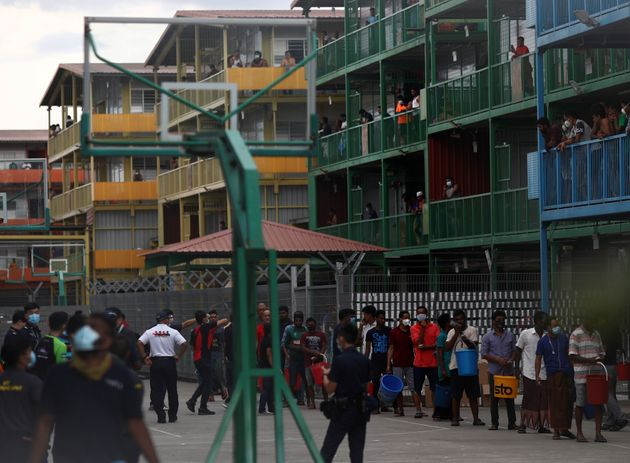 Migrant workers lining up to collect food at the Punggol S11 dormitory in Singapore during the coronavirus...