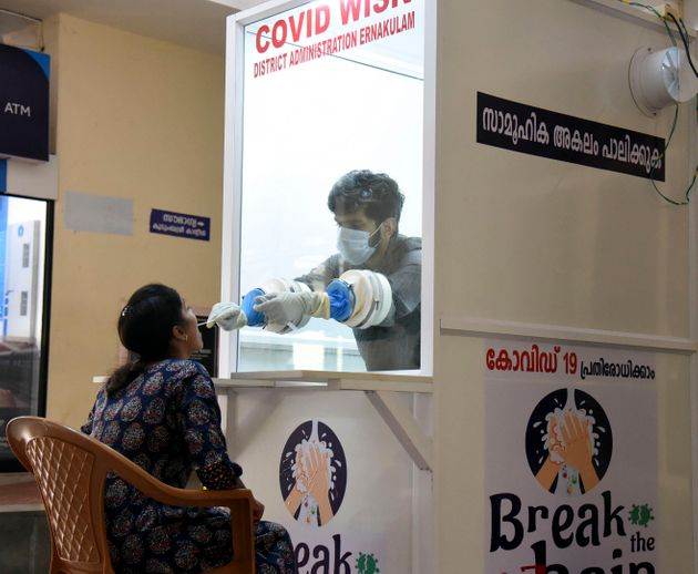 A medical staff collects samples from a woman at a new walk-in coronavirus testing kiosk at Ernakulam...
